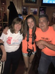 Caroline sits with some of her supporters at a fundraiser for Team Caroline and RSDSA (CRPS RSD)