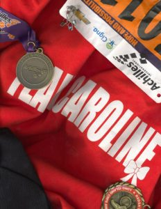 Caroline, a young adult photographer with CRPS, depicts her team shirt for the awareness walks she has participated in along with her medals