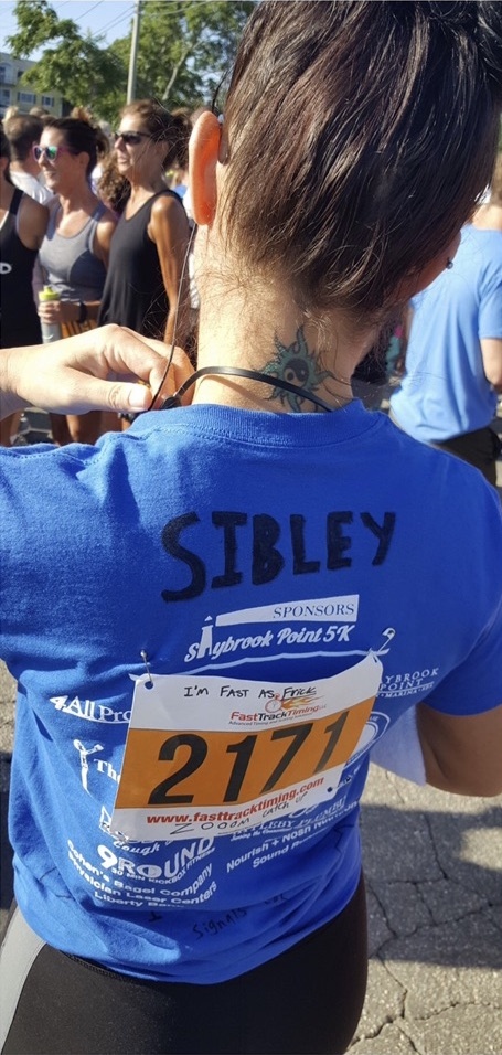 Back of a woman's blue shirt after a race