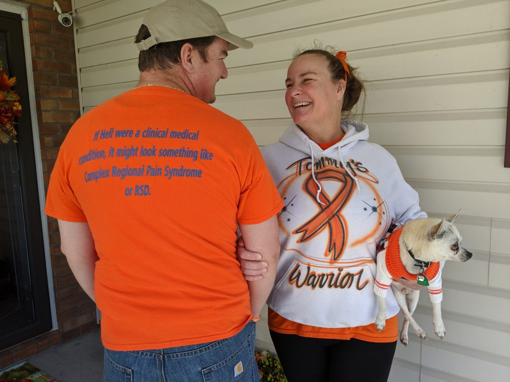 Woman wearing a white shirt and holding a dog smiling at a man wearing an orange shirt